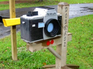 Okay, this is a Nikon camera mailbox made from wood. Guess the mail comes in from the side.