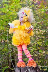 "For some reason, I think this is more of a mashup costume between Big Bird and Effie Trinket. Hell, this girl almost seems like she's about to choose District 12 tributes for the Hunger Games. Like she's saying, ""Primrose Everdeen."""