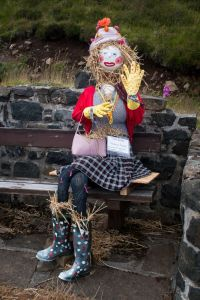 She's just sitting on the bench. Too bad she has straw in her boots. Then again, she's a scarecrow.