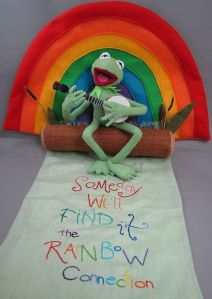 Has a plush banjo playing Kermit on a log with swamp plants. Not to mention the rainbow embroidered lyrics.