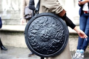 Well, that's a large ornate purse she has. Sure it's leather, but its shield seems like it was made from metal.