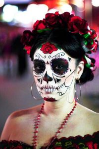 This woman has roses in her hair as well as an intricate skull makeup scheme. Absolutely stunning.