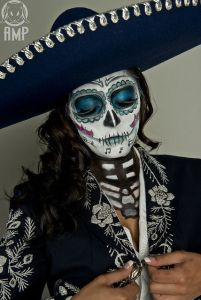 This woman wears a sombrero that matches her outfit and makeup. And she has it buttoned to show some of her ribs.