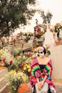Well, at least she's in a cemetery, perhaps to honor her dead relatives. Yet, I do like her multicolored serape.