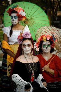 Here we have 3 generations of a family in their skull face makeup and flowers. Two of them carry parasols in hand.