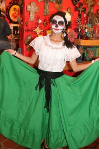 This woman just wears a traditional Mexican outfit. Just a white top and green skirt.