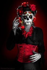 She even has the bony fingers to show it. Yet, she wears roses to go with her red corset.