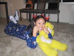 She's dressed in a footie pajama outfit with pigtails. Also has her Care Bear to snuggle with.