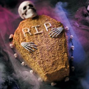 You may not be able to eat the hands and skull. But a coffin shape cake isn't a hard shape to achieve.