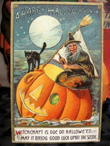 "From Tracy's Toys: ""Where has she come from, and why didn't she just fly, as would have been traditional? Where is she going, in her broom masted pumpkin boat? Is she a good witch or a bad witch? She's smiling, but I suppose that's not a sure thing: the witch in Hansel and Gretel was probably smiling warmly right up to the time she tried to cook and eat her little visitors. Is that cat safe? Why isn't he in the boat too? I'm worried he's going to fall off. And just how seaworthy is that pumpkin boat? Is there any danger of fish nibbling away the bottom? Won't water come through the face holes? Seems like a major design flaw there. This is definitely a postcard that raises lots of questions."""