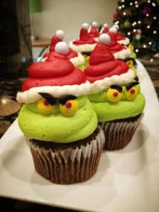 These almost could be taken for Santa cupcakes. Except for the fact that they're green with yellow eyes beneath the Santa hat.