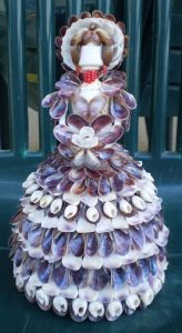 Her dress is made from purple mussels. Not sure about the bonnet. But even her hair is made from seashells.