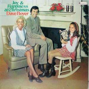 "From Flashbak: ""I don't need to tell you that your wife with fake tan and your crummy living room shouldn't be on the cover of your album; clearly, this wasn't conveyed to Dave Boyer. For the curious, his daughter is holding ""Reach Out"" a hip version of the New Testament."""