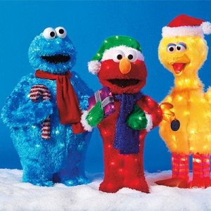These lawn decorations consist of Cookie Monster, Elmo, and Big Bird. Still, Big Bird is taller while Cookie shouldn't hold a candy cane.
