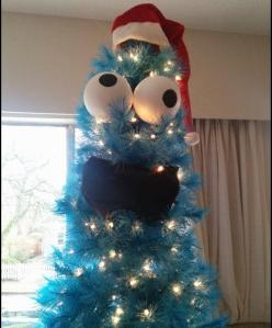 Well, this seems like a rather simple way to decorate Christmas tree. Just eyes, mouth, lights, and Santa hat on an artificial blue Christmas tree and you're good to go.