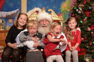 Yeah, this kids don't like sitting on Santa's lap. Meanwhile the girls beside him just smile for the camera.