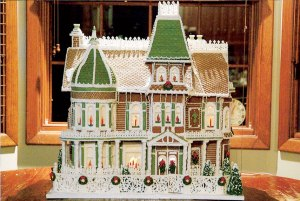 This one has wreath decorations on the fence and candles in the window. Love the lattice work on the roof.