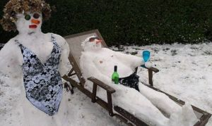Another snow couple in swimsuits. The guy seems to recline with a drink in hand.