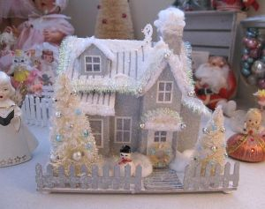 This one has silver trimming on the roof. Whether it's to express snow or decoration, I'm not sure. Like how the smoke comes from the chimney though.
