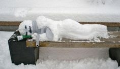 Seems like he's a homeless snowman sleeping on a bench. And he has some booze with him.