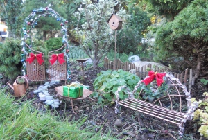 The arch and bench are covered in tinsel and bows. The arch even has lights.