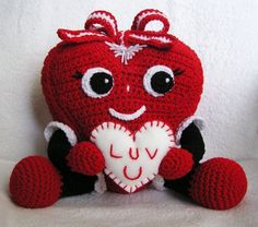 Here the heart is holding a cute little valentine. Love the bow on the head. Adorable.