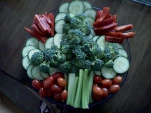 Comprises of broccoli, celery, and cucumber slices. Surrounded by tomato slices and cherry tomatoes.