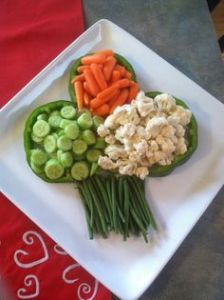 Includes cucumber slices, baby carrots, and cauliflower inside a shamrock made from peppers. Also uses green beans for a stem.
