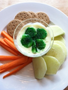 Includes a shamrock in the center for dip. Snacks include carrots, crackers, and cucumber slices.