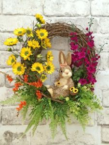 If you like bright spring flowers, this wreath is certainly for you. But don't mind the bunny who's only passing time.