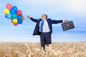 Businessman in wheat field with briefcase and balloons