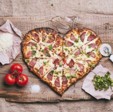 heart-shaped-pizza-and-ingredients-on-cutting-board-royalty-free-image-1579107262